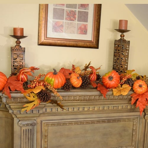 Fall leaf garland decorated with pumpkins and berries. It's the perfect autumn mantel decor idea!